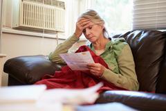 Worried Senior Woman Sitting On Sofa Looking At Bills - stock photo