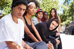 Gang Of Young People In Urban Setting Sitting On Bench - stock photo