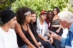 Senior Man Talking With Gang Of Young People - stock photo