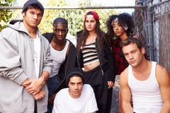 Gang Of Young People In Urban Setting Standing By Fence - stock photo