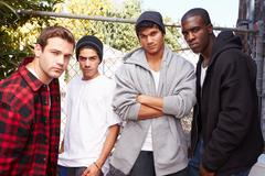 Group Of Young Men In Urban Setting Standing By Fence Stock Photos