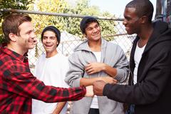 Group Of Young Men Greeting One Another In Urban Setting Stock Photos