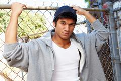 Portrait Of Young Man In Urban Setting Standing By Fence Stock Photos