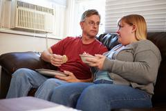 Couple With Poor Diet Sitting On Sofa Eating Meal Stock Photos