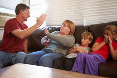 Physically Abusive Father With Family On Sofa Stock Photos