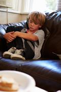 Unhappy Boy Sitting On Sofa At Home - stock photo