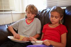 Children With Poor Diet Eating Meal On Sofa At Home Stock Photos