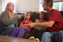 Family Sitting On Sofa With Parents Arguing - stock photo