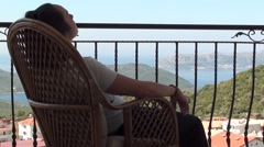 Woman resting in a rattan chair with wonderful view 2 Stock Footage