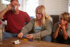 Parents Sit On Sofa With Children Taking Drugs And Drinking - stock photo