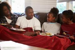 Family With Poor Diet Sitting On Sofa Eating Meal Stock Photos