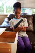 Girl Playing With Parent's Gun She Has Found At Home - stock photo