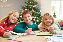 Three Children Writing Letters To Santa Together Stock Photos