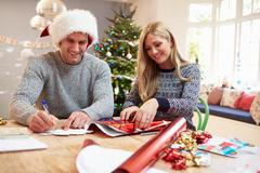 Couple Wrapping Christmas Gifts At Home Stock Photos