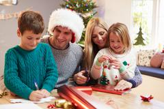 Family Wrapping Christmas Gifts At Home Stock Photos