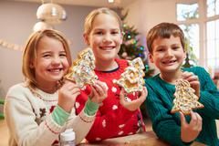 Three Children Showing Decorated Christmas Cookies Stock Photos