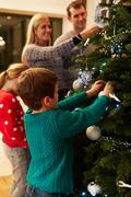 Family Decorating Christmas Tree At Home Together Stock Photos