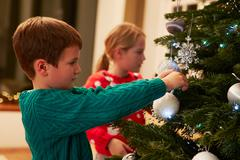 Children Decorating Christmas Tree At Home - stock photo