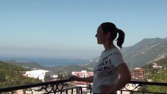 Woman with ponytail enjoys view from the balcony Stock Footage