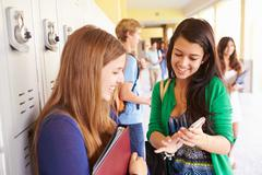 High School Students By Lockers Looking At Mobile Phone - stock photo