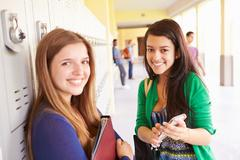 High School Students By Lockers Looking At Mobile Phone Stock Photos