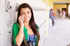 Female High School Student By Lockers Using Mobile Phone Stock Photos
