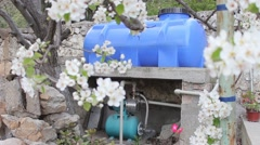 A small, electrically powered pump and plastic tank. Stock Footage