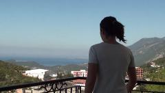 Woman with ponytail gets out to the balcony to enjoy the sea view 2 - stock footage
