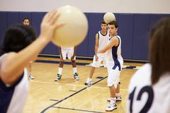 High School Students Playing Dodge Ball In Gym Stock Photos