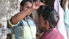Men dyeing hair at the street hair salon in Mumbai. Stock Footage