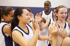 High School Sports Team Celebrating In Gym Stock Photos