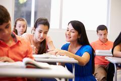 Teacher Helping Female High School Student In Classroom - stock photo