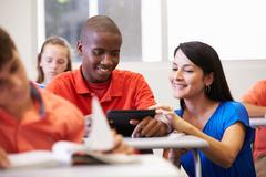 Teacher Helping Male High School Student In Classroom - stock photo