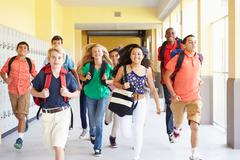 Group Of High School Students Running Along Corridor Stock Photos