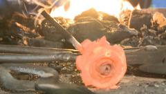Blacksmith forges a red-hot metal rose Stock Footage