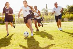 Members Of Female High School Soccer Playing Match Stock Photos