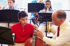 Boy Learning To Play Cello In High School Orchestra - stock photo