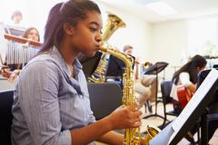 Female Pupil Playing Saxophone In High School Orchestra Stock Photos