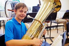 Male Pupil Playing Tuba In High School Orchestra - stock photo