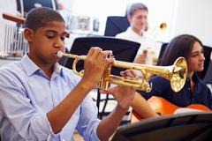 Male Pupil Playing Trumpet In High School Orchestra Stock Photos