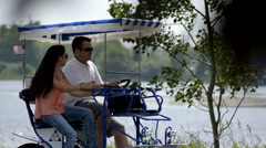 Couple riding a peddle cart having fun 4 Stock Footage