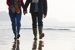 Close Up Of Senior Couple Walking Along Winter Beach - stock photo