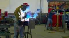 Welders and a mechanic working in factory Stock Footage