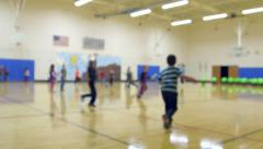 Blurred shot of schoolchildren playing in gym class Stock Footage