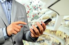 Business Man using Mobile Cell Phone in The Modern office building. Stock Photos