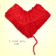 Heart-shaped coil of red yarn and text I love you, mom Stock Photos