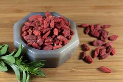 Dry goji berries in a stone mortar. - stock photo