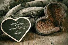 Happy mothers day in a heart-shaped chalkboard on a rustic background Stock Photos