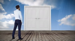 Door opening to blue sky watched by businessman Stock Footage