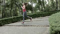 Young woman in sports outfit running pass the camera at the park Stock Footage